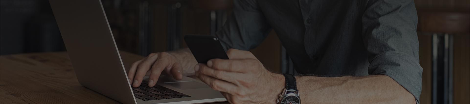 starsza osoba z zegarkiem przy laptopie
